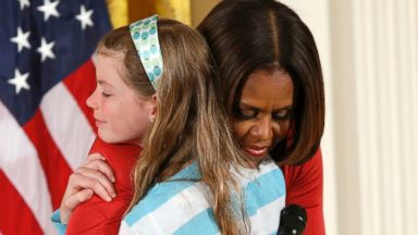 PHOTO: First Lady Michelle Obama hugs Charlotte Bell, 10, who gave the first lady her fathers resume and said he had been out of work for three years, at the White Houses annual Take Our Daughters and Sons to Work Day in Washington, April 24, 2014.