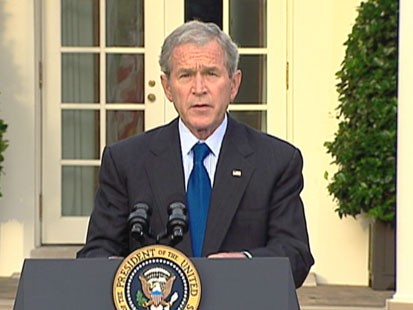 A picture of President Bush speaking in front of the White House.
