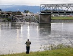 PHOTO: A person looks from the south bank of the Skagit River across to the collapsed portion of the Interstate 5 bridge, May 24, 2013, in Mount Vernon, Wash.