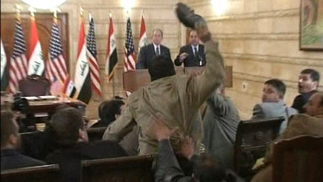 PHOTO: A man, center, throws a shoe at US President George W. Bush, background left, during a news conference with Iraq Prime Minister in Baghdad, Iraq, Dec. 14, 2008