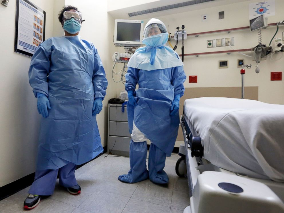 PHOTO: Belkys Fortune, left, and Teressa Celia, pose in protective suits in an isolation room during a demonstration of procedures for possible Ebola patients at Bellevue Hospital, New York, Oct. 8, 2014.