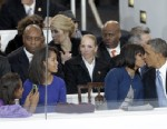 PHOTO: President Barack Obama kisses first lady Michelle Obama as their daughters, Sasha, left, and Malia, second from left, watch during the inaugural parade, Jan. 21, 2013, in Washington.