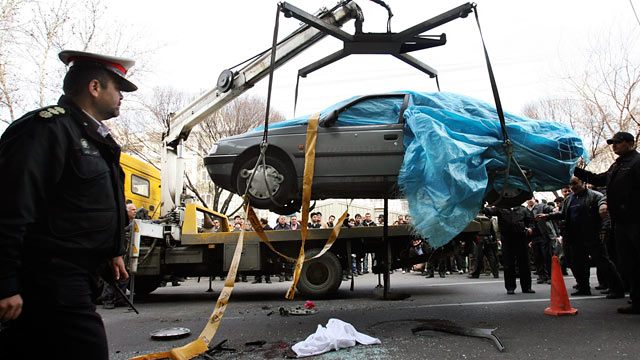 PHOTO: People gather around a car as it is removed by a mobile crane in Tehran, Iran, Jan. 11, 2012.