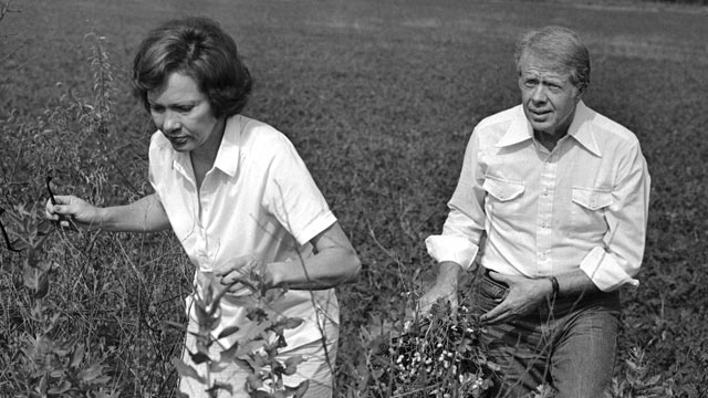 PHOTO:President Jimmy Carter carries a peanut plant as he follows his wife Rosalynn from the field at their Webster County, Ga., farm on Aug. 19, 1978.