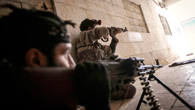 PHOTO: Free Syrian Army fighters aim their weapons at the entrance of a building during heavy clashes with government forces in Aleppo, Syria, Dec. 5, 2012.