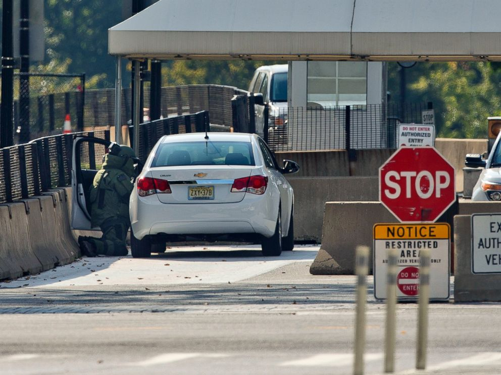 PHOTO: An explosive technician in a bomb suit kneels as he searches a vehicle near the entrance to White House in Washington, Saturday, Sept. 20, 2014.