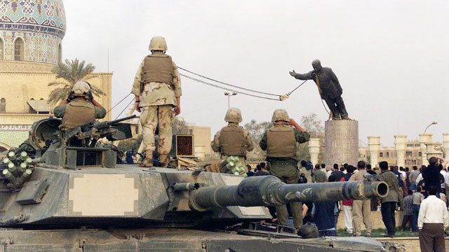 PHOTO: U.S marines and Iraqis are seen on April 9, 2003 as the statue of Iraqi dictator Saddam Hussein is toppled at al-Fardous square in Baghdad, Iraq.