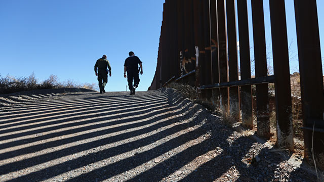 PHOTO: U.S. Customs and Border Protection personnel walk along a section of a recently constructed fence at the U.S.-Mexico border, Feb. 26, 2013, in Nogales, Ariz.