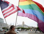 PHOTO: A gay activist holds American and gay pride flags in San Francisco, California.