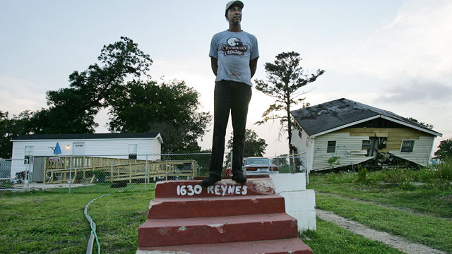 PHOTO: Warren Schexnader stands on the steps of his old home in front of another destroyed home, right, and the FEMA trailer he is currently living in, left, June 8, 2007 in New Orleans.