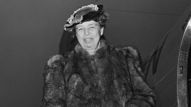 PHOTO:Portrait of US First Lady Eleanor Roosevelt circa 1945, wearing a fur coat and holding a purse, smiling while standing on a ramp after exiting an airplane.