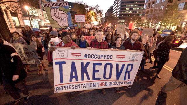 PHOTO: Protesters from Occupy DC march past the Washington Convention Center during a demonstration against the billionaire conservative donor Koch brothers and Americans for Prosperity, Washington, DC, Nov. 4, 2011.