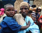 PHOTO: An unidentified Rwandan woman holds a child, April 30, 1994 as others file past her in Tanzania. Two hundred fifty thousand refugees cross the border to flee the advance of the Tutsi Rwandese Patriotic Front.