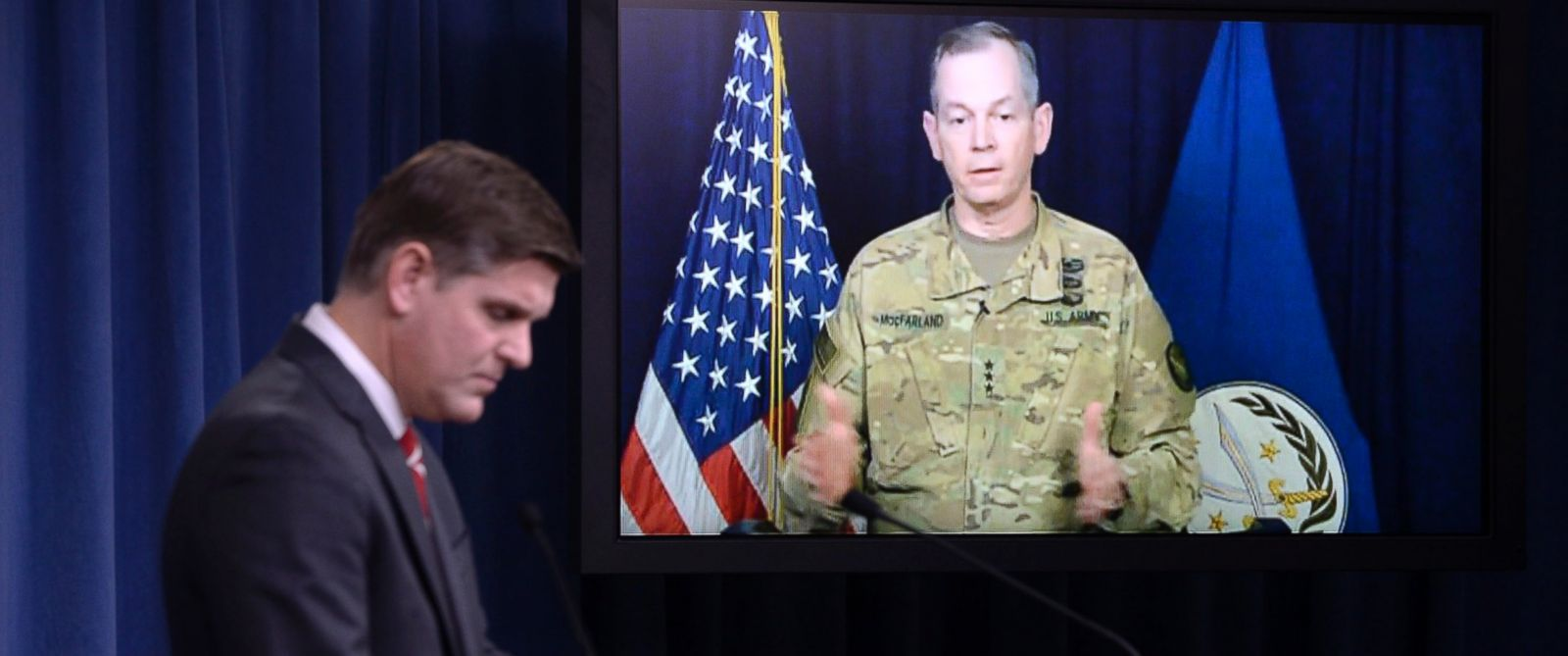 PHOTO: Combined Joint Task Force Commander Army Lt. Gen. Sean MacFarland speaks via teleconference from Baghdad, Iraq as Pentagon Press Secretary Peter Cook listens during a media briefing at the Pentagon, Feb. 1, 2016 in Arlington, Va.
