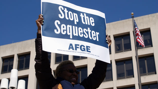 PHOTO: A protester holds a sign at a demonstration against sequestration of the US Department of Labor in Washington, March 20, 2013.