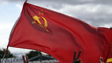 PHOTO: A man flashes the victory sign and waves a socialist flag at a political event organized by the French communist party September 18, 2011 in La Courneuve, outside Paris.