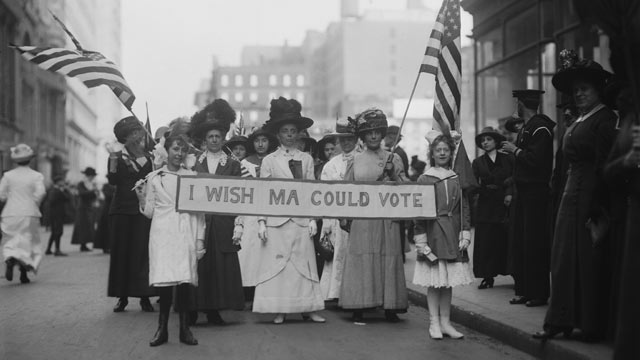 PHOTO: A group of suffragettes campaigning for the right to vote in the United States, march in a parade carrying a banner reading, 'I Wish Ma Could Vote,' circa 1913.