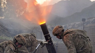 PHOTO: US army soldiers from Bravo company 2nd Batallion 27th Infantry Regiment fire 120 mm mortar rounds towards insurgent positions at Outpost Monti in Kunar province, Sept. 17, 2011.