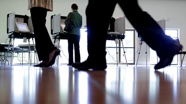 PHOTO: Polling place workers assists voters with a digital voting machine during the presidential primary election at Saints Peter & Paul Antiochian Orthodox Christian Church April 3, 2012 in Potomac, Maryland.