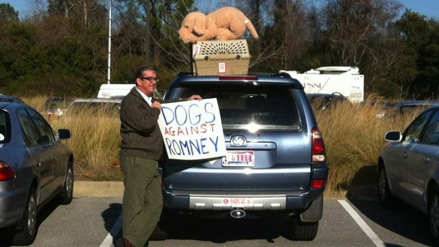 "PHOTO: An unidentified man holds up a sign reading, ""Dogs against Romney"" in this handout photo."