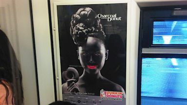 PHOTO: An advertisement poster of smiling woman with bright pink lips in blackface makeup holding doughnut