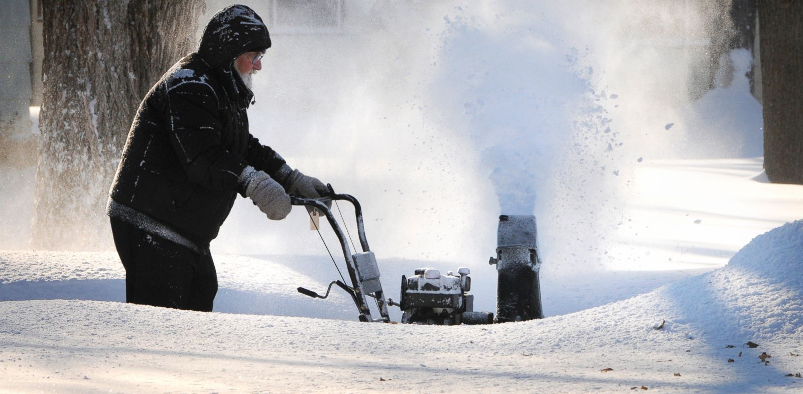 PHOTO: A resident cleans inches of new-fallen snow from his driveway in St. Cloud, Minn., Jan. 18, 2014.