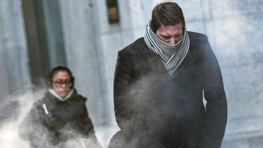 PHOTO: A man clenches his fists as he walks past a steam vent on a cold morning in New York, Jan. 7, 2014.