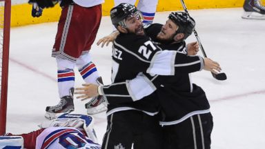 PHOTO: Los Angeles Kings defenseman Alec Martinez, center, celebrates with left wing Kyle Clifford as they win in double overtime during the second overtime period in Game 5 of the Stanley Cup finals, Friday, June 13, 2014, in Los Angeles.