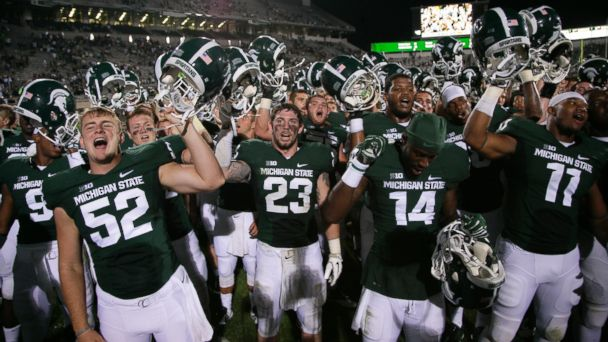 Michigan State players, including Taybor Pepper (52), Chris Frey (23), Tony Lippett (14), and Jamal Lyles (11), celebrate following a 45-7 win over Jacksonville State in an NCAA college football game, Friday, Aug. 29, 2014, in East Lansing, Mich.