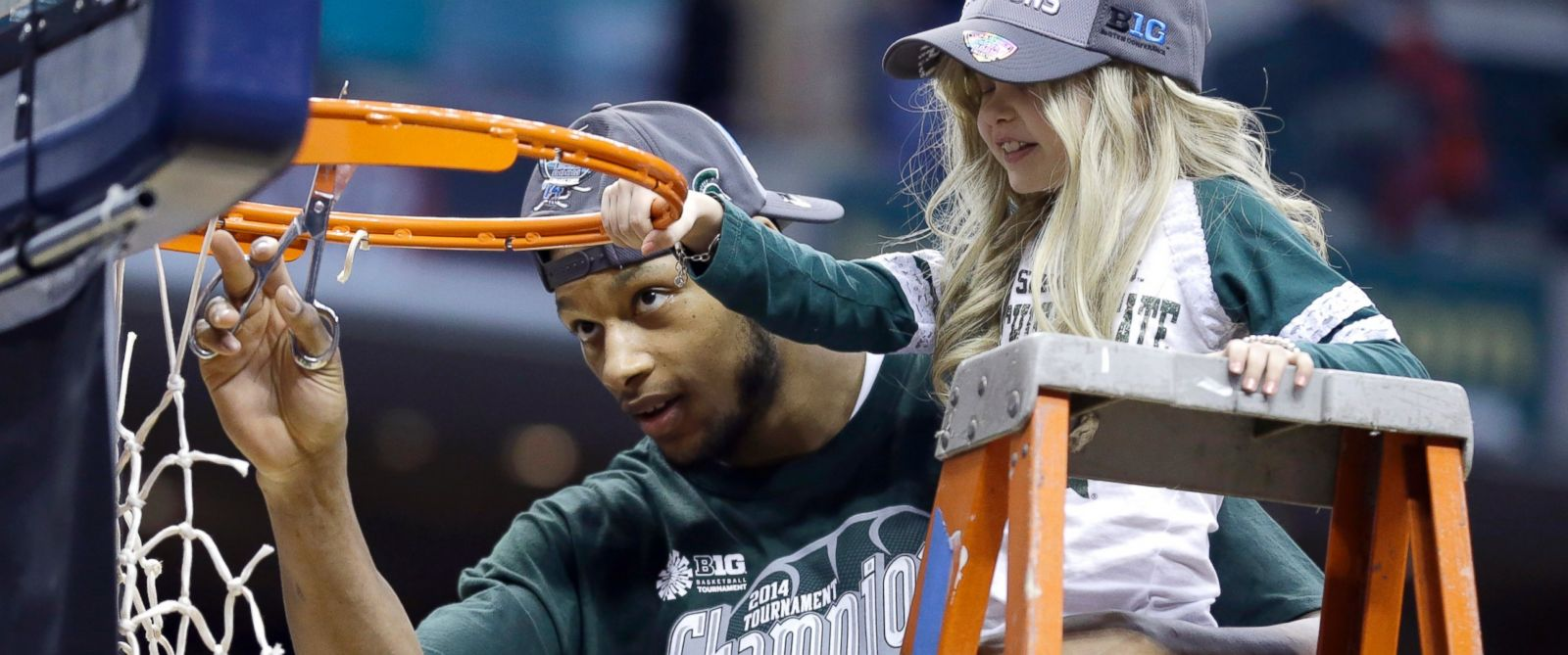 PHOTO: Michigan State forward Adreian Payne, left, cuts the net with Lacey Holsworth, March 16, 2014.