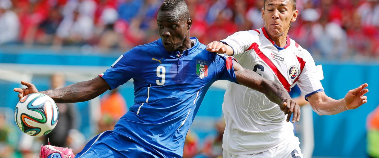 PHOTO: Italys Mario Balotelli, left, gets in a shot despite the challenge of Costa Ricas Oscar Duarte during the group D World Cup soccer match between Italy and Costa Rica at the Arena Pernambuco in Recife, Brazil, June 20, 2014.