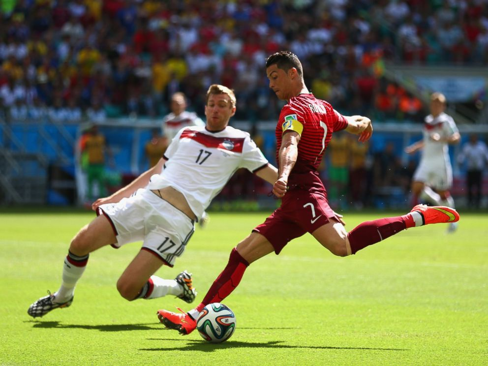 PHOTO: Cristiano Ronaldo of Portugal shoots against Per Mertesacker of Germany during the 2014 FIFA World Cup Brazil Group G match between Germany and Portugal at Arena Fonte Nova on June 16, 2014 in Salvador, Brazil.