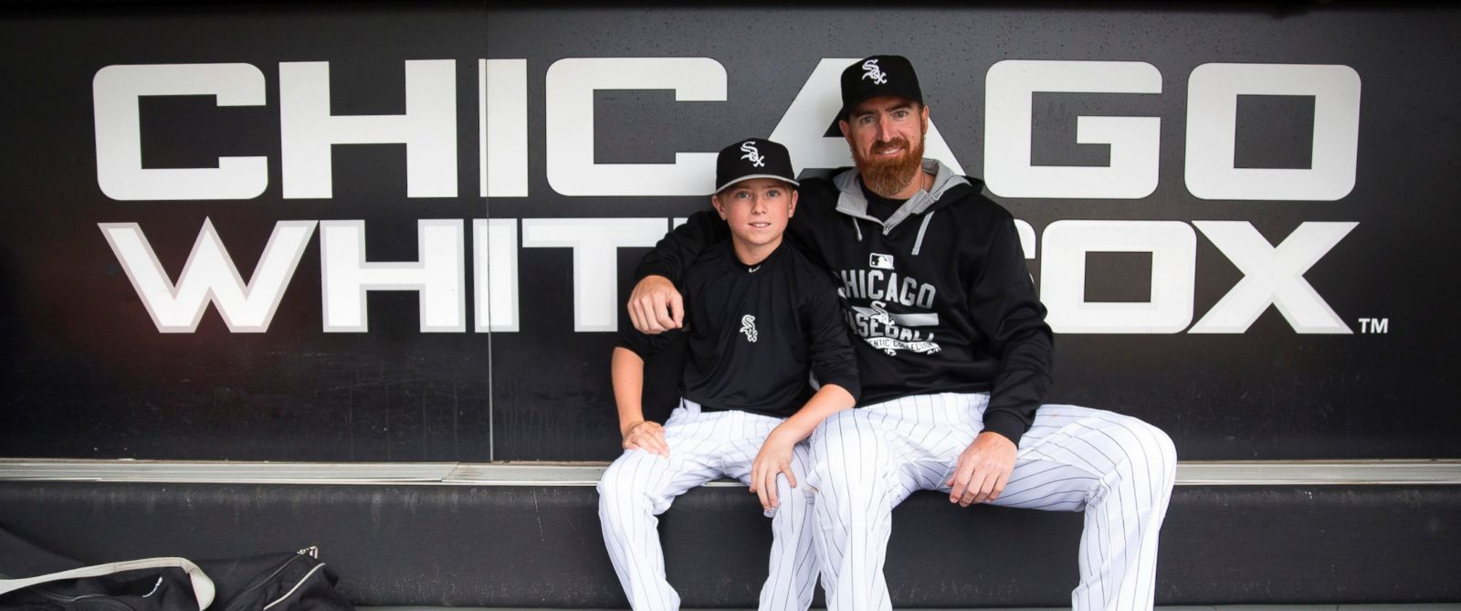 PHOTO: Chicago White Sox designated hitter Adam LaRoche sits with his son Drake, 13, in the White Sox dugout at U.S. Cellular Field before a game against the Houston Astros on June 8, 2015 in Chicago.