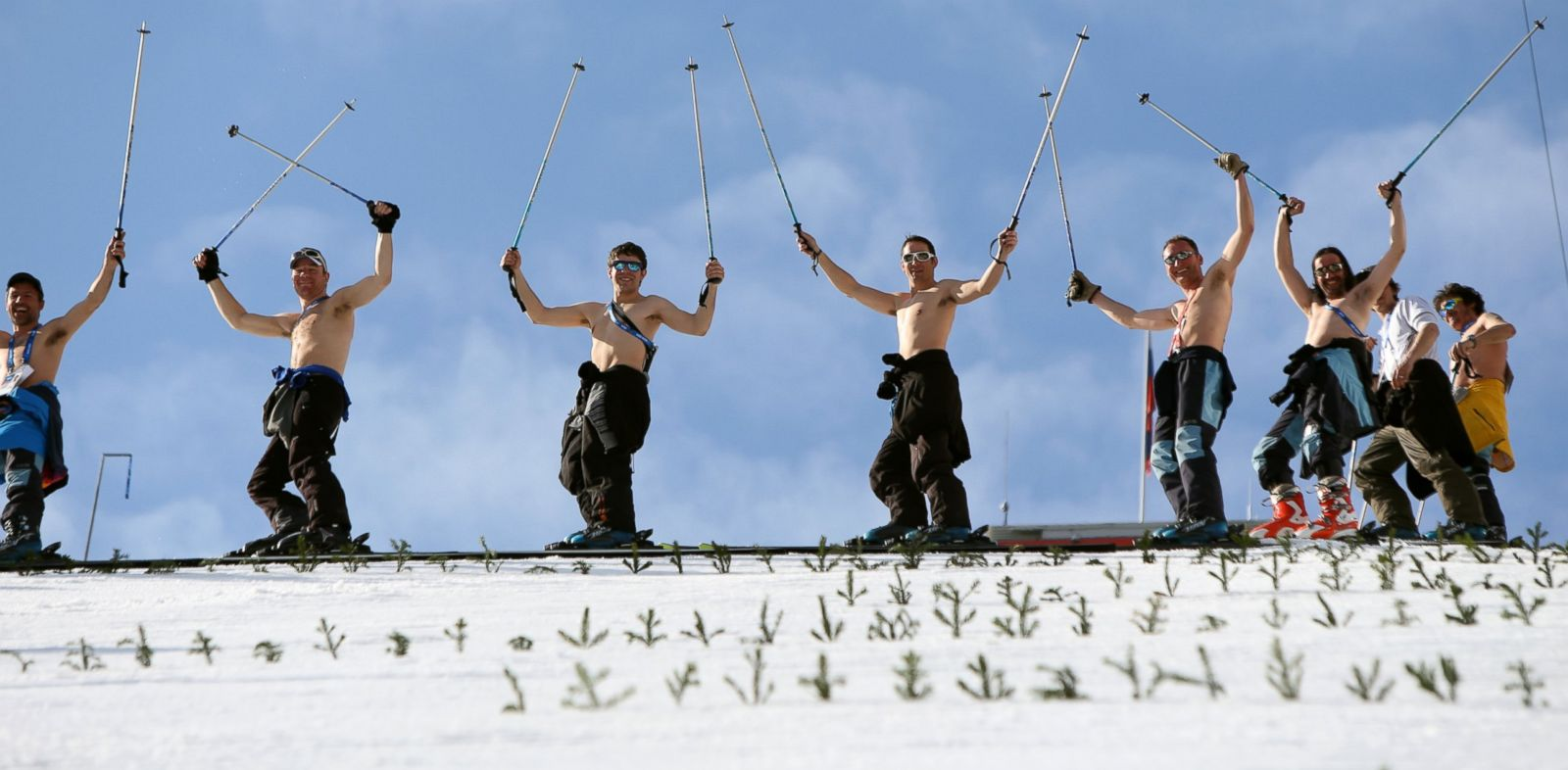 PHOTO:Course workers take off their shirts to enjoy the warm weather as they prepare the landing hill before the mens Nordic combined normal hill training jump at the RusSki Gorki Jump Center at the 2014 Sochi Winter Olympics.