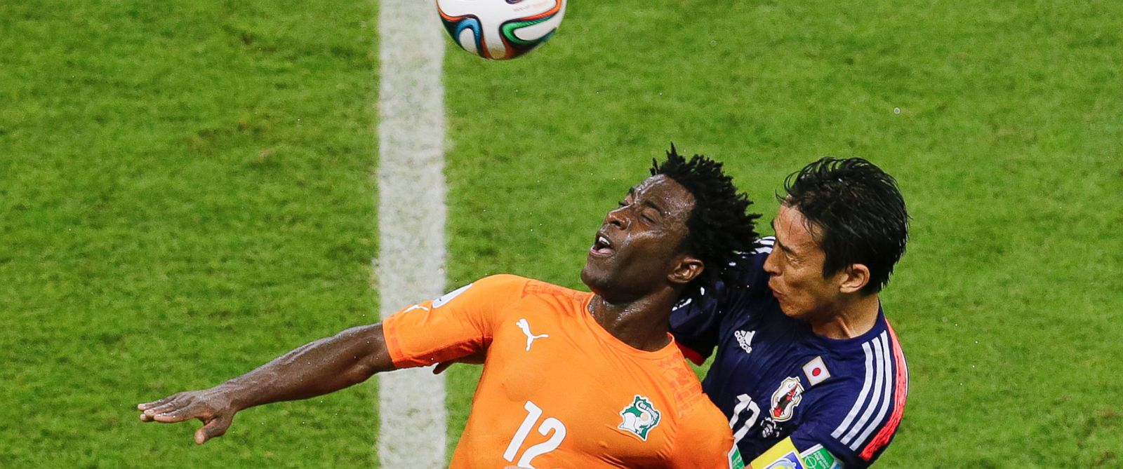PHOTO: Japans Makoto Hasebe, right, and Ivory Coasts Wilfried Bony go for a header during the group C World Cup soccer match between Ivory Coast and Japan at the Arena Pernambuco in Recife, Brazil, Saturday, June 14, 2014.