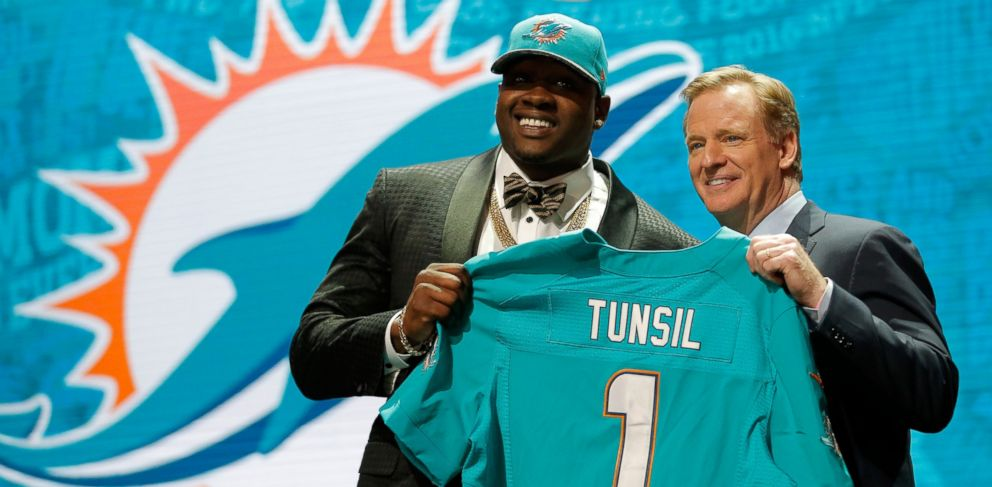 PHOTO: Laremy Tunsil holds up a jersey with NFL Commissioner Roger Goodell after being picked by the Miami Dolphins during the first round of the 2016 NFL Draft at Roosevelt University on April 28, 2016 in Chicago.