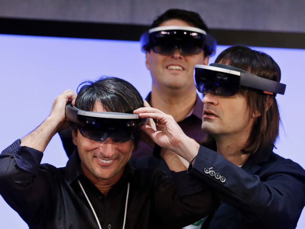 PHOTO: Microsofts Joe Belfiore (L) smiles as he tries on a Hololens device with colleagues Alex Kipman (R) and Terry Myerson following an event demonstrating new features of Windows 10 at the companys headquarters on Jan. 21, 2015, in Redmond, Wash.