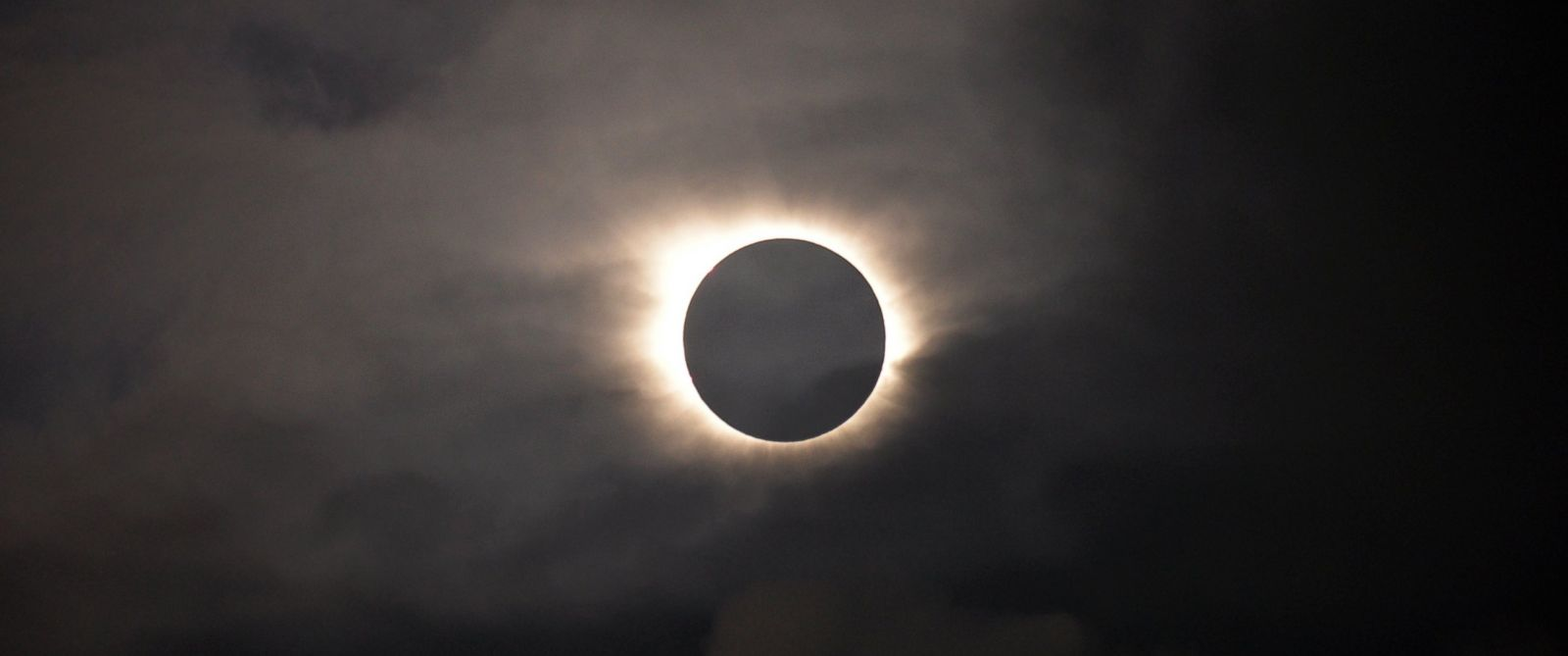PHOTO: A total solar eclipse is visible through the clouds as seen from Vagar on the Faeroe Islands, March 20, 2015.
