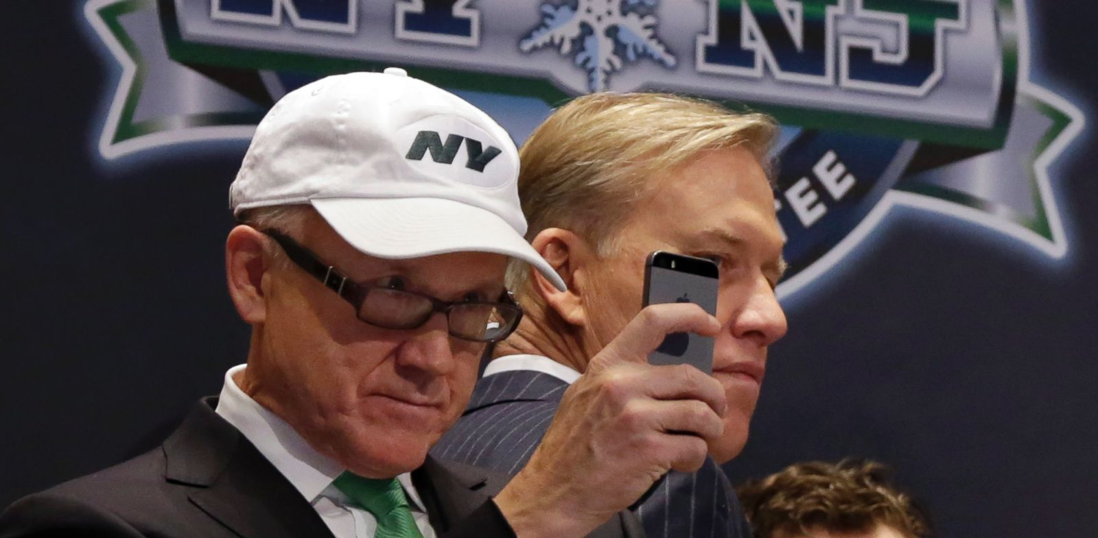 PHOTO: New York Jets owner Woody Johnson, left, uses his mobile phone