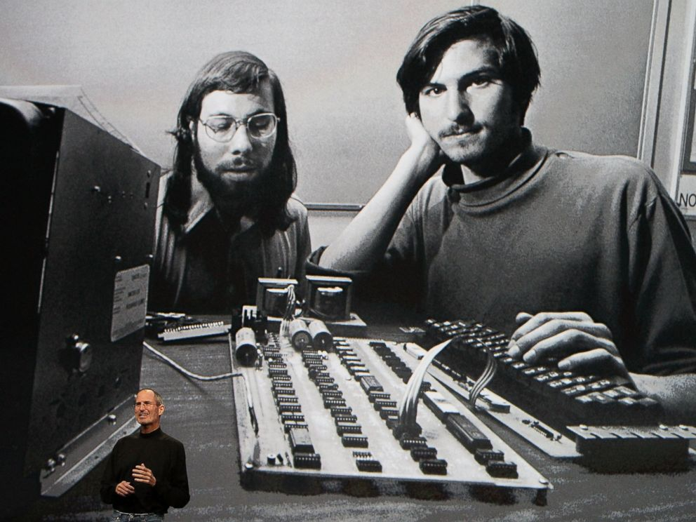 PHOTO: Steve Jobs, chief executive officer of Apple Inc., right, speaks in front of a file photograph of himself and Apple co-founder Steve Wozniak during the launch of the Apple iPad tablet in San Francisco, Calif., on Jan. 27, 2010.