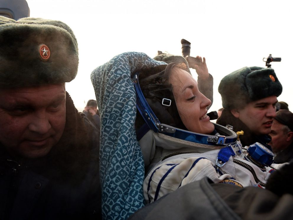 PHOTO: Russias space agency ground personnel help Russian cosmonaut Yelena Serova after the landing of the Soyuz TMA-10M capsule in the city Karaganda in Kazakhstan, March 12, 2015.