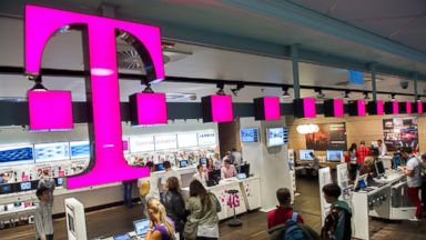 PHOTO: Customers inspect mobile communication devices inside a T-Mobile store, April 24, 2012.