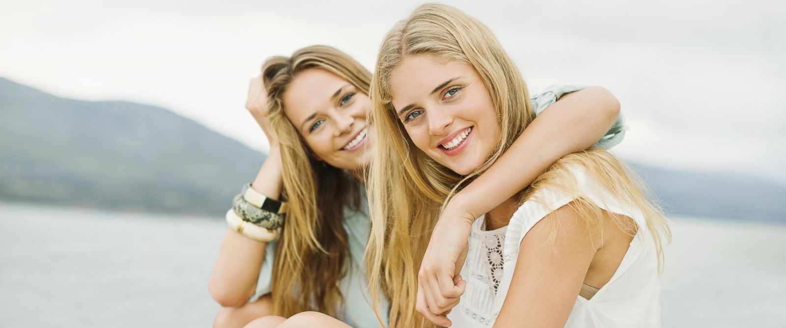 PHOTO: Two friends with blonde hair smile for a portrait.