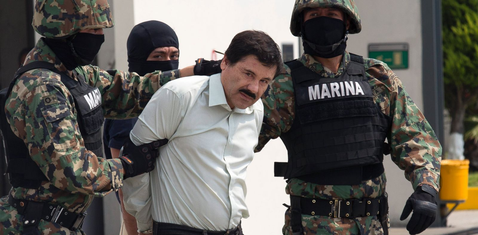 "PHOTO: Drug trafficker Joaquin ""El Chapo"" Guzman is escorted to a helicopter by Mexican security forces at Mexicos International Airport in Mexico City, Mexico on Feb. 22, 2014."