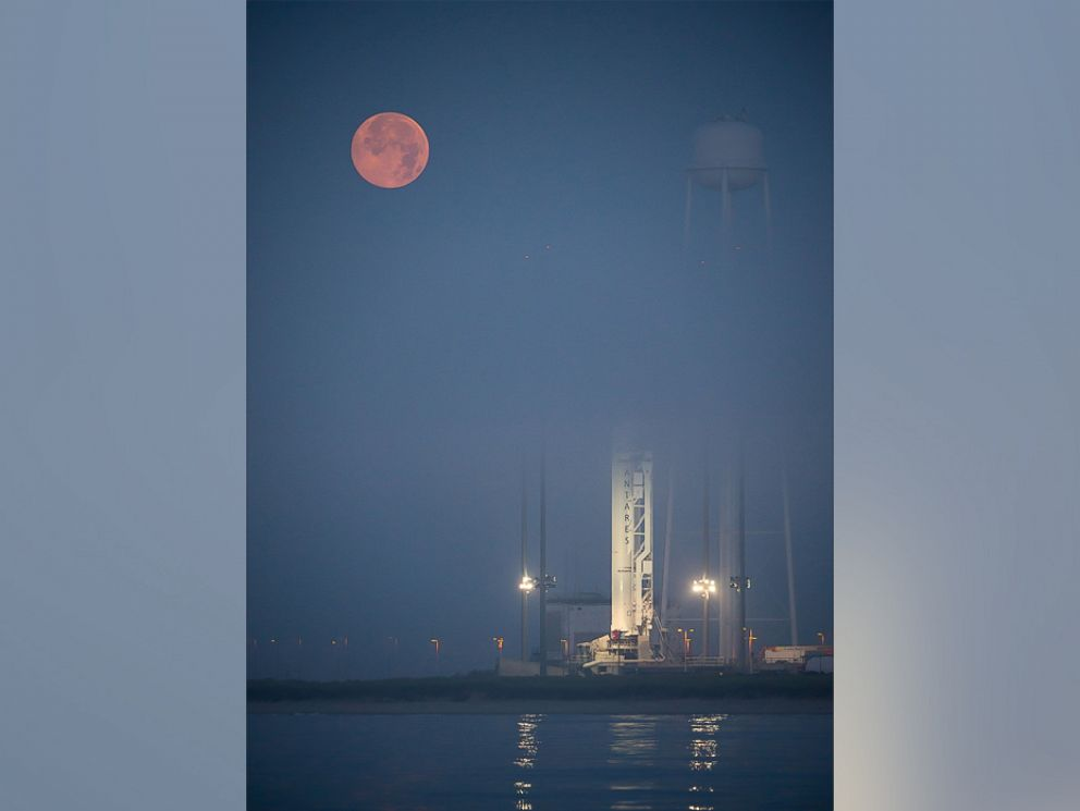 PHOTO: The full Moon sets in the fog behind the Orbital Sciences Corporation Antares rocket, with the Cygnus spacecraft onboard, Saturday, July 12, 2014, launch Pad-0A, NASAs Wallops Flight Facility in Virginia.