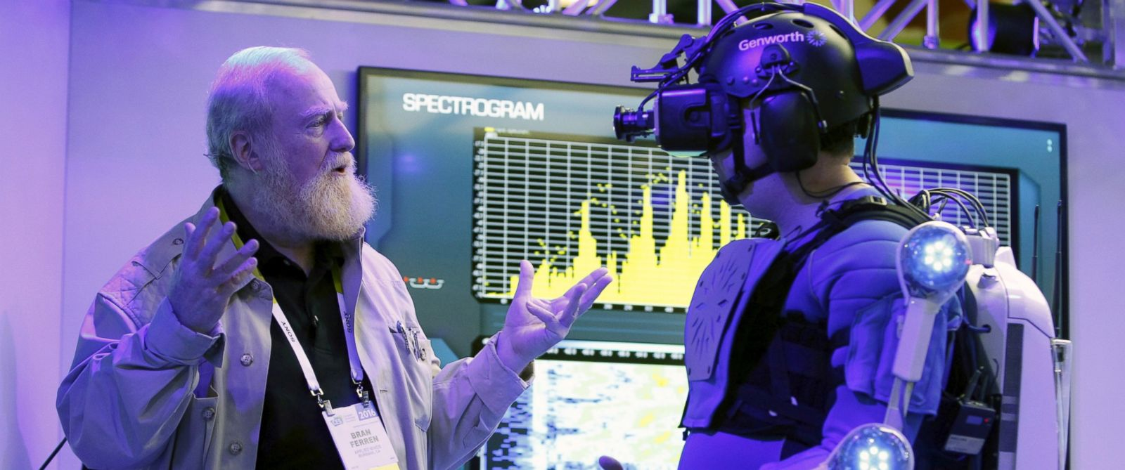PHOTO: Bran Ferren founder of Applied Minds, talks to a journalist dressed in an R70i aging suit during a preview of the Genworth booth at the 2016 CES trade show in Las Vegas, Jan. 5, 2016.