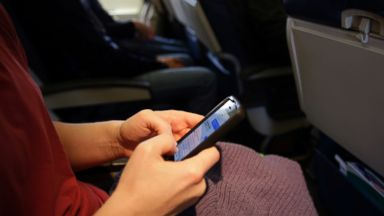 PHOTO: In this Oct. 31, 201 file photo, a passenger checks her cell phone after boarding a flight.