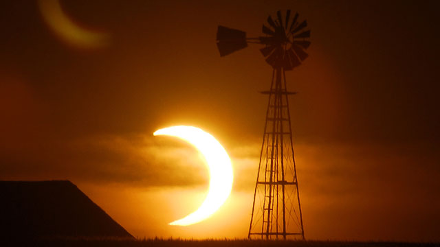 PHOTO: The sun sets behind a barn and windmill on Sunday, May 20, 2012, southwest of Ellis, Kans, during a partial solar eclipse.