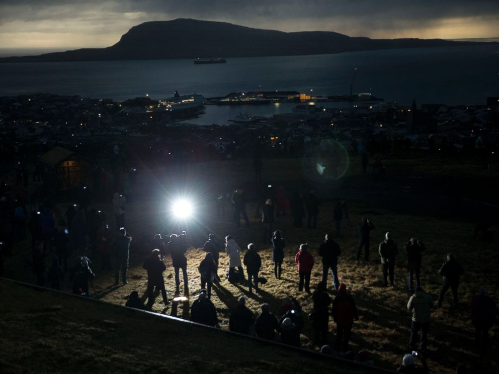PHOTO: People watch in darkness during the totality of a solar eclipse on as seen from a hill beside a hotel on the edge of the city overlooking Torshavn, the capital city of the Faeroe Islands, March 20, 2015.
