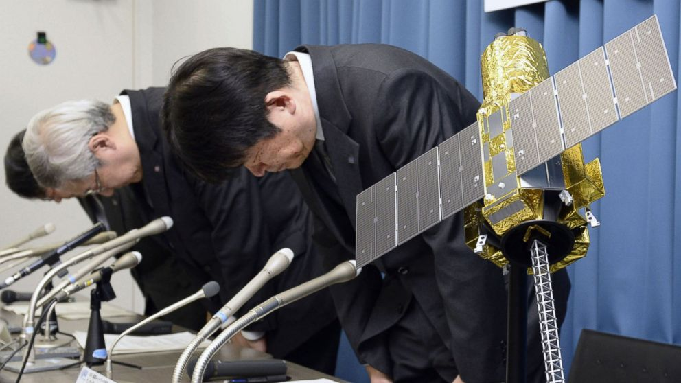 PHOTO: Officials of the Japan Aerospace Exploration Agency bow beside the model of an X-ray astronomy satellite called Hitomi in the agency in Tokyo, Japan, April 28, 2016.